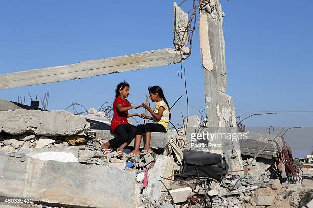 Palestinian girls play on the rubble of houses which was destroyed during the 50-day Israeli war against Gaza in the summer of 2014, in the village...
