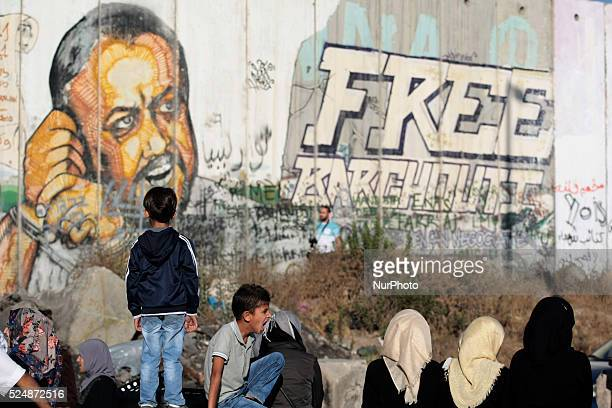 Palestinian girls sitting boy yawns while the other boy standing on the cement blocks in front of the Israeli wall where a Marwan Barghouti painting...
