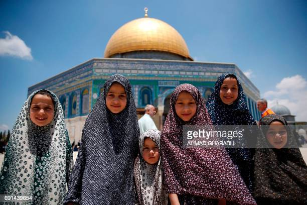 Palestinian girls stand infront the Dome of the Rock as they attend the first Friday prayers of the Muslim holy month of Ramadan at Jerusalem's...