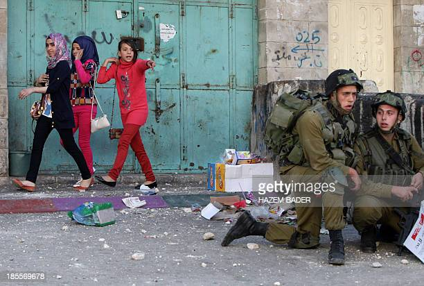 Palestinian girls walk past as Israeli soldiers take position during clashes with Palestinian stone throwers nearby an Israeli army checkpoint in the...