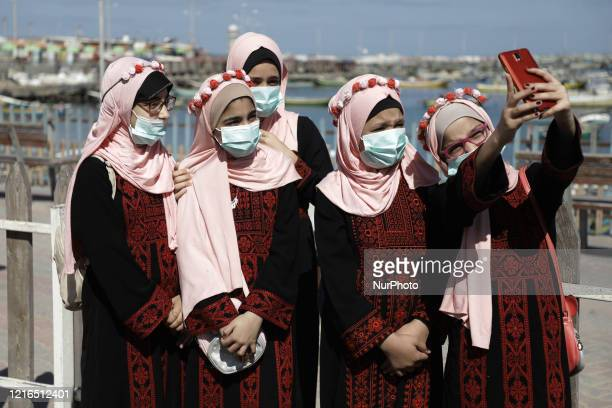 Palestinian girls wearing protective masks take a selfie at the seaport of Gaza City on May 31 amid concerns about the spread of the novel...