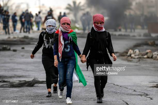 Palestinian girls with their faces covered with traditional chequered keffiyehs walk during clashes with Israeli forces following a demonstration...