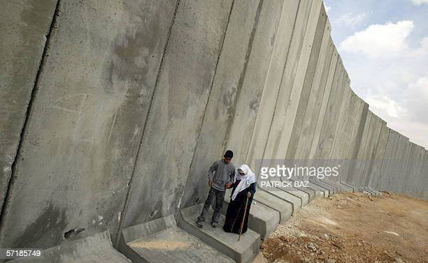 Palestinian grandson helps his grandmother from the Khatib family as she walks along the base of the cement controversial Israeli 'separation...