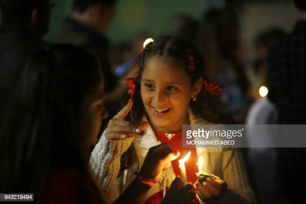 A Palestinian Greek Orthodox Christian holds a candle lit from the 'Holy Fire' at the Church of Saint Porphyrius in Gaza City on early April 8 2018...