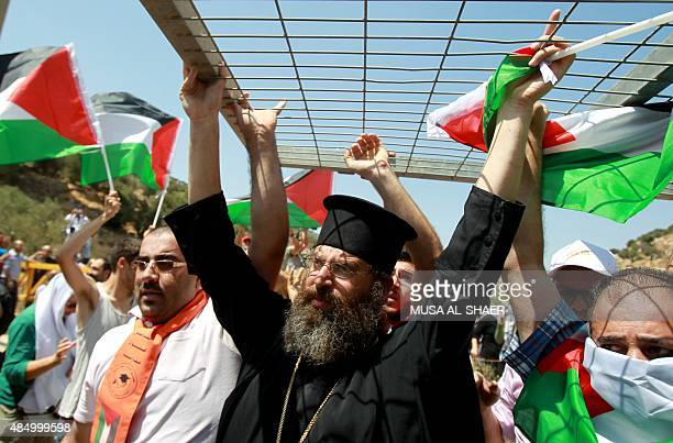 A Palestinian Greek Orthodox priest and other protesters carry an Israeli military gate during a demonstration against land confiscation for the...