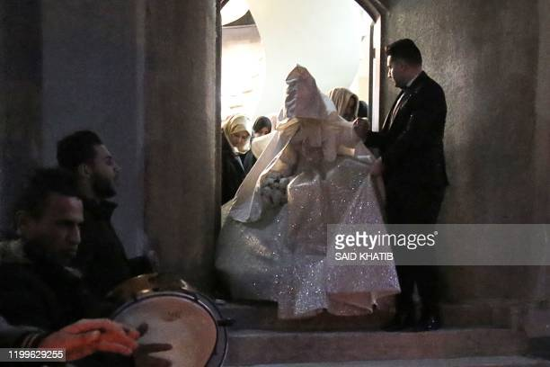 Palestinian groom Ahmed Soboh accompanies his wife ahead of their wedding ceremony in the southern Gaza Strip refugee camp of Rafah on February 5...