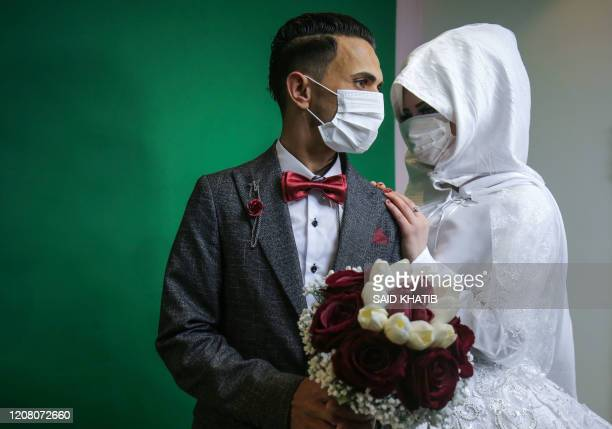 Palestinian groom Mohamed abu Daga and his bride Israa wear protective masks amid the COVID-19 epidemic, during a photoshoot at a studio before their...