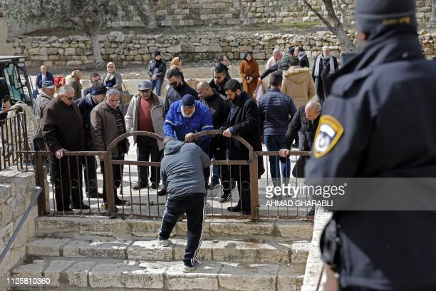 A Palestinian guard opens the small gate lock at the Al Aqsa mosque compound in Jerusalem's Old City after Israeli police accepted to give it back on...
