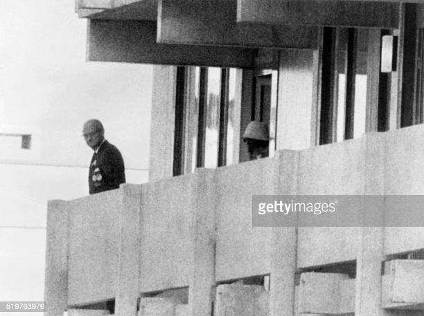 A Palestinian guerilla member appears on the balcony of the Israeli house watching an official on September 05 1972 at the Munich Olympic village A...