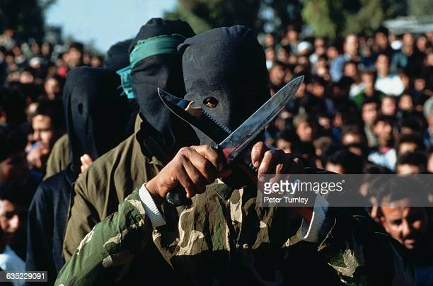 A Palestinian guerilla wearing a mask over his face crosses two daggers at a Hamas rally in Gaza