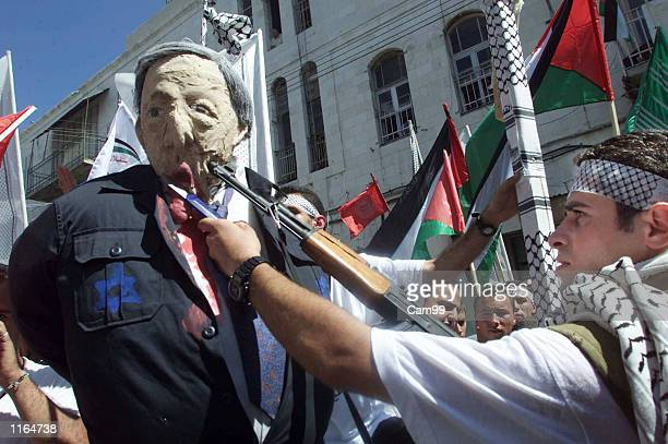 Palestinian gunman holds an automatic rifle and a knife to an effigy of Israeli Prime Minister Ariel Sharon September 29 2001 during a demonstration...