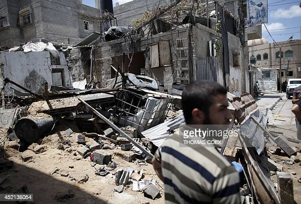 A Palestinian Hamas member stands guard in front of a destroyed building following an Israeli air strike on July 14 2014 in Gaza City Israel kept up...
