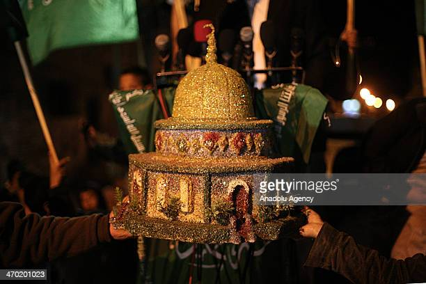 Palestinian Hamas movement supporters hold a model of Dome of the Rock during a demonstration against the Israeli Judaization schemes in alAqsa...