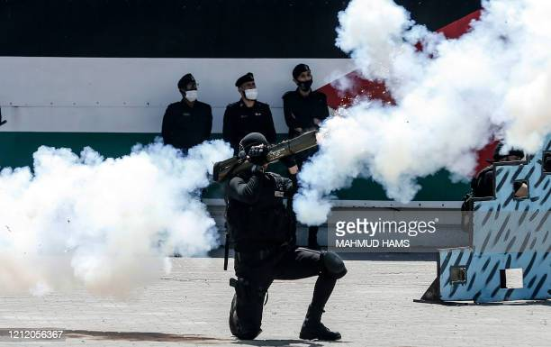Palestinian Hamas police cadet fires a weapon as he demonstrates his skills during a graduation ceremony the from Police Academy amid concerns about...