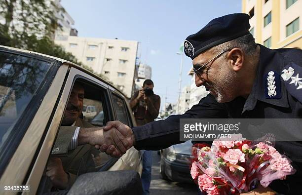 Palestinian Hamas police chief Abu Obeida elJarraah hands out flowers to drivers in the occasion of the Eid alAdha or Feast of the Sacrifice on...