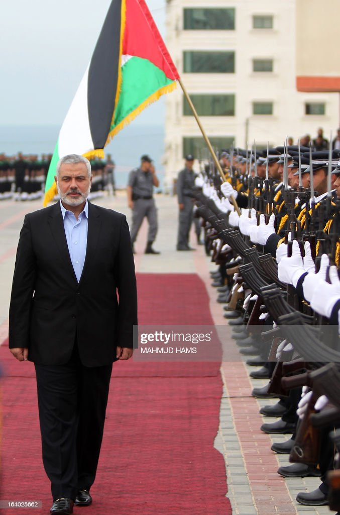 Palestinian Hamas prime minister Ismail Haniya reviews an honour guard during the graduation ceremony of Hamas security forces in Gaza City on March 19, 2013.