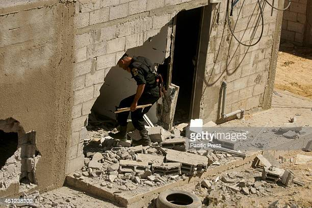 Palestinian Hamas security force personnel inspects the site of an Israeli air strike on Khan Yunis, in the central Gaza Strip. The Israeli air force...