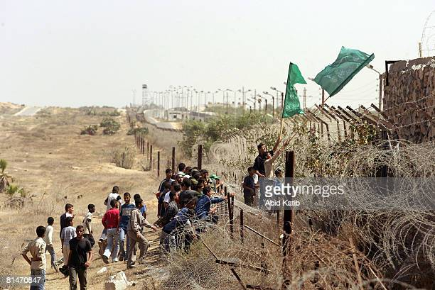 Palestinian Hamas supporters hold Hamas flags as they attend a demonstration against the blockade on Gaza on June 6 2008 at the RafahEgypt Crossing...