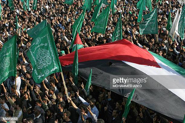 Palestinian Hamas supporters shout slogans and wave their party's flag and a huge Palestinian flag during a protest in Gaza City on November 14 2008...