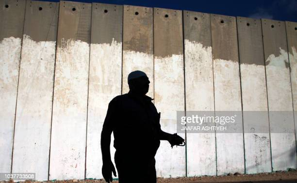 Palestinian Hani Amer walks towards his house after crossing through a little gate on September 22 erected in the West Bank village of Mashah along...