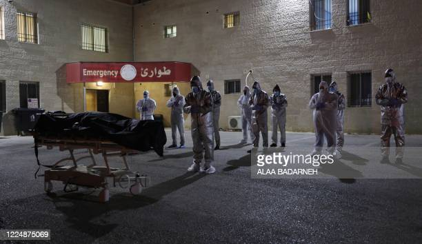 Palestinian health workers recite a prayer in front of the body of a woman who died after contracting the COVID19 disease caused by the novel...
