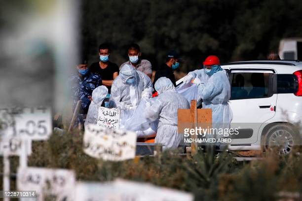 Palestinian health workers, wearing protective clothes, carry the body of a doctor, who died from the coronavirus, ahead of his burial in a cemetary...