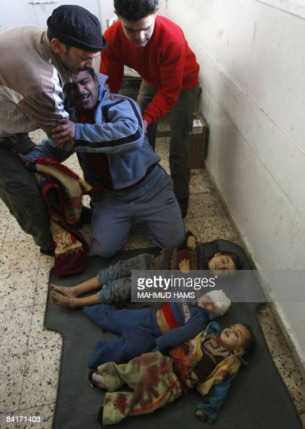 Palestinian Hilmi alSamuli mourns over the bodies of his two sons and nephew killed by an Israeli tank shell early on January 5 upon their arrival at...