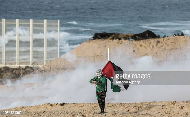 Palestinian holds a Palestinian flag as Israeli forces intervene protesters with gas bombs during the maritime protest against Israels ongoing...