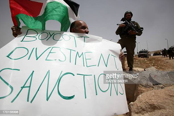 A Palestinian holds a placard reading in English Boycott divestment sanctions as part of a protest during which they try to set up a tent on June 8...