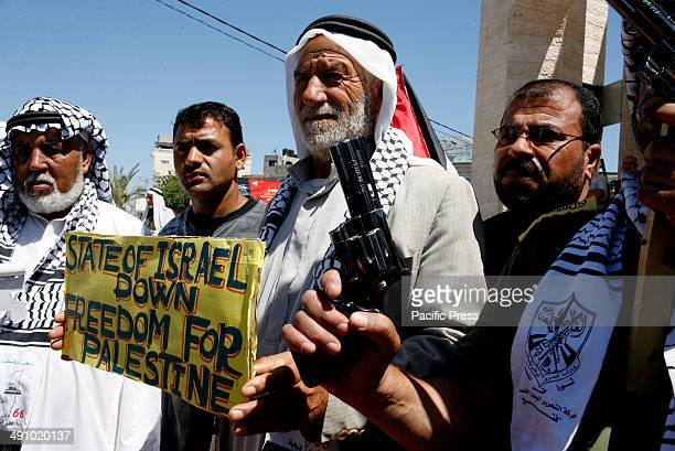 Palestinian holds a sign as he takes part in a rally ahead of the 66th anniversary of Nakba, in Rafah in the southern Gaza Strip. Palestinians will...