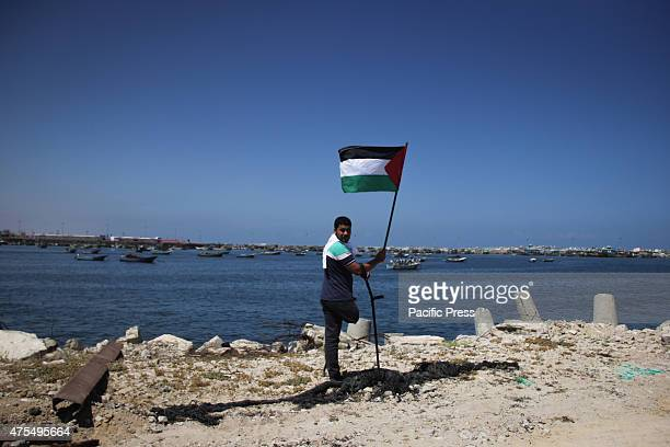 Palestinian holds flag Palestinians organized boat parade with flags during a rally marking the 5th anniversary of the Mavi Marmara Gaza flotilla...