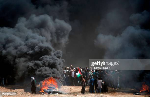 Palestinian holds his national flag in the smoke billowing from burning tyres during clashes with Israeli forces near the border between the Gaza...