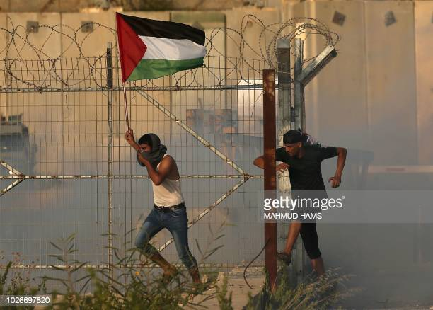 Palestinian holds up a national flag and runs through tear gas fired by Israeli forces during a protest at the Erez crossing with Israel on September...