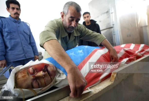 Palestinian hospital worker covers the body of American peace activist Rachel Corrie with an American flag at the Najar hospital March 17 2003 in the...