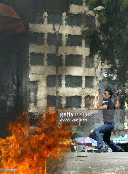 A Palestinian hurls stones at Israeli soldiers during clashes in the northern West Bank city of Nablus 18 August 2004 Israeli Prime Minister Ariel...