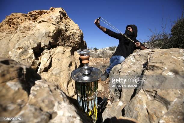Palestinian hurls stones at Israeli troops during a protest against Israeli land seizures for Jewish settlements in alMazraah alGharbiyah village...