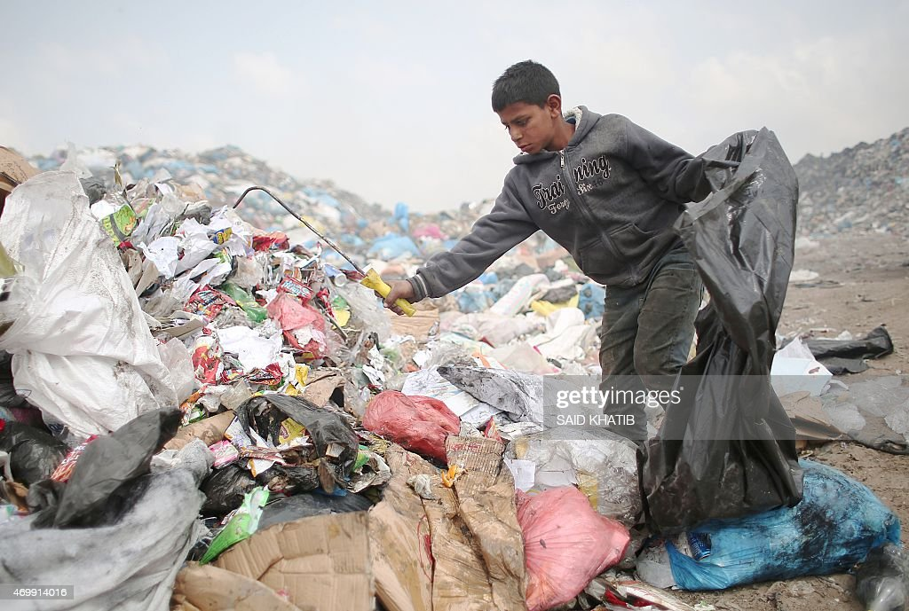 Palestinian Hussein Al-Najjar, 14-years-old, searches through a pile of trash for recyclable waste and other items in hope to be able to sell them, at a garbage dump in Rafah, in the southern Gaza Strip on April 16, 2015.