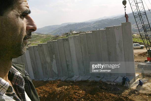Palestinian Hussein Oheish looks from his rooftop at Israeli workers building Israel's security barrier February 12 2004 between east Jerusalem and...