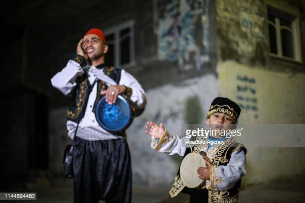 Palestinian Ibrahim alKarnawi and his son Mohammed are seen as they play with a tambourine and a darbuka to awake Palestinians for predawn meal of...
