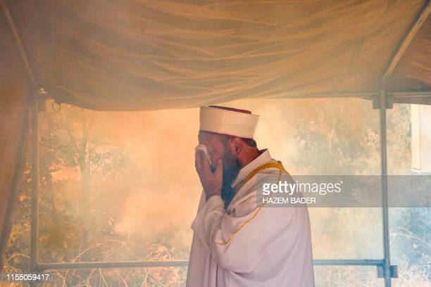Palestinian imam covers his face from tear gas fumes fired by Israeli security forces, while leading a prayer inside a protest tent erected during a...