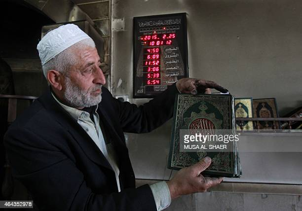 Palestinian Imam Ibrahim Abu Luha shows a burnt Koran Islam's holy book after a mosque was torched overnight on February 25 2015 in the West Bank...