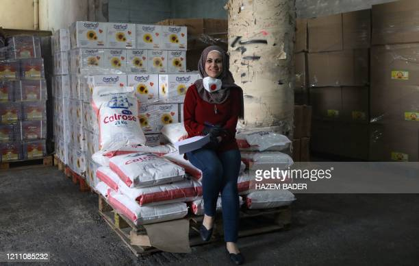 Palestinian Iman Abu Areesh the coordinator of the Emergency and Aid committee of the Hebron governor's office, poses for a picture beside stacks of...
