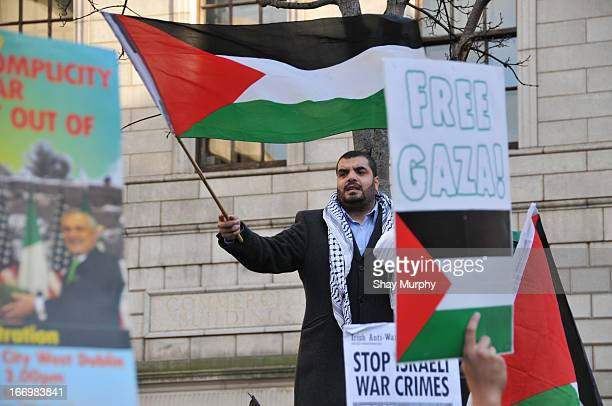 Palestinian in Dublin calling for the end of the blockade of Gaza, waving the Palestinian flag.