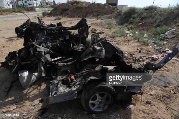 A Palestinian inspect a destroyed car after Israeli air strike in alShejaeiya neighbouhood in the east Gaza City Gaza Strip 17 June 2018