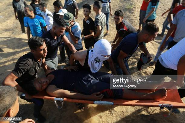 Palestinian is being carried after he was injured by Israeli soldiers during Great March of Return demonstration near GazaIsrael border in Rafah Gaza...