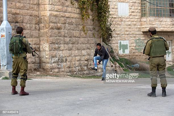 A Palestinian is checked by Israeli soldiers patrolling the streets of the West Bank city of Hebron on December 15 2015 The UN voiced deep concern on...
