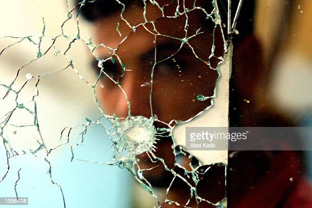 Palestinian is shown in his barber shop mirror damaged by Israeli bullets August 27 2002 in the Khan Younis refugee camp in southern Gaza Strip