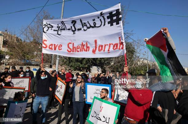 Palestinian, Israeli, and foreign activists lift banners and placards during a demonstration against Israeli occupation and settlement activity in...