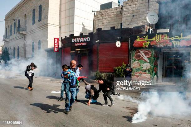 Palestinian journalist carries away a child as other photojournalists assist a falling woman as they walk amidst tear gas canisters during a...