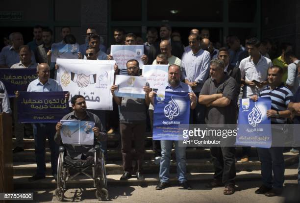 Palestinian journalists hold banners reading in Arabic ''Being a journalsit is not a crime'' and ''No to closing AlJazeera channel'' during a sitin...
